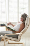 Pregnant Woman Reading Book On Chair. Side view of happy young pregnant women reading book on chair Stock Images