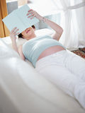 Pregnant woman reading book at home stock photo