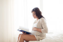 Pregnant woman reading book at home bedroom Stock Photos