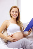 Pregnant woman reading book at home Royalty Free Stock Image