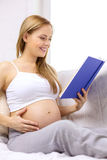 Pregnant woman reading book at home Royalty Free Stock Images