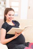 Pregnant woman reading a book at home Stock Photo