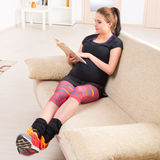 Pregnant woman reading a book at home Stock Photos