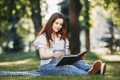 Pregnant woman reading a book to her child at park royalty free stock photo