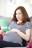 Pregnant Woman Reading Leaflet With Medical Advice Stock Photography