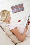 Pregnant woman reading magazine Royalty Free Stock Photos