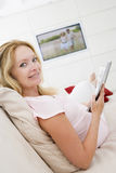 Pregnant woman reading magazine Stock Images