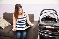 Pregnant woman reading stroller instructions Stock Image