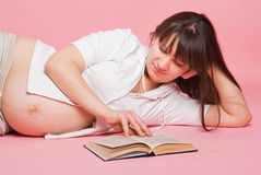 Pregnant woman reads the book Stock Photo