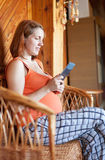 Pregnant woman reads e-book. In home interior royalty free stock photography