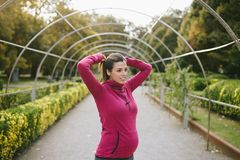 Pregnant woman ready for exercising in autumn outdoor. Pregnant sporty woman getting ready for fitness workout outdoor. Female motivated gravid athlete lacing Stock Photo