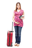 Pregnant woman ready to travel. Full length portrait of a beautiful young Hispanic pregnant woman holding a passport and plane ticket, ready to travel Royalty Free Stock Image