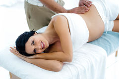Pregnant woman receiving a back massage from masseur. Pregnant women receiving a back massage from masseur at home royalty free stock photos