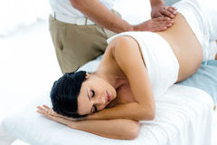 Pregnant woman receiving a back massage from masseur. Pregnant women receiving a back massage from masseur at home stock photo