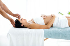Pregnant woman receiving a head massage from masseur. Pregnant women receiving a head massage from masseur at home Royalty Free Stock Photos