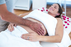 Pregnant woman receiving massage. Pregnant women lying on bed receiving massage in spa Royalty Free Stock Image