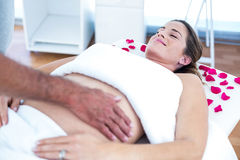 Pregnant woman receiving massage. Pregnant women receiving massage from masseur in spa Royalty Free Stock Photography