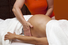 Pregnant woman receiving relaxing massage Stock Photo