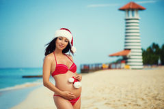 Pregnant woman in a red bathing suit and a Christmas santa hat on the sea coast Royalty Free Stock Image