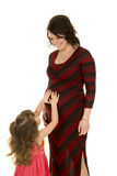 Pregnant woman in red and black dress looking at daughter touching belly stock photography
