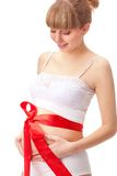 Pregnant woman  with red bow on belly Stock Photos