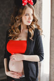Pregnant woman with red bow. Royalty Free Stock Image