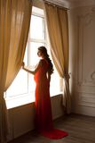 Pregnant woman in red dress Stock Photos