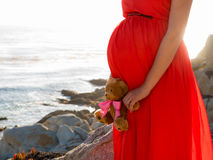 Pregnant woman in red dress standing by ocean with toy Stock Photo