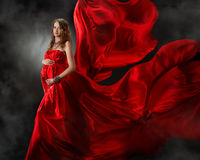 Pregnant woman in red flying dress Stock Photography