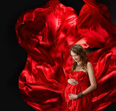 Pregnant woman in red flying dress Royalty Free Stock Image