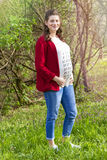 Pregnant woman in red jacket with calendar on her T-shirt. Outdoor in the park stock photography