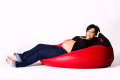 Pregnant woman on a red pillow Royalty Free Stock Image