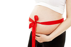 Pregnant woman with red ribbon on belly Stock Images