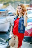 Pregnant woman in red shirt, hat, sunglasses and black trousers at yacht marina of Malta.  royalty free stock photos