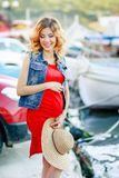 Pregnant woman in red shirt, hat, sunglasses and black trousers at yacht marina of Malta.  stock photos