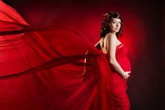Pregnant woman in red waving dress. Looking at camera Stock Photography