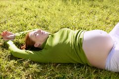 Pregnant woman redhead laying on grass. Garden park relaxed stock image