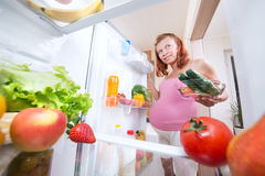 Pregnant woman and refrigerator with health food Stock Image