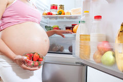 Pregnant woman and refrigerator with health food Stock Photo