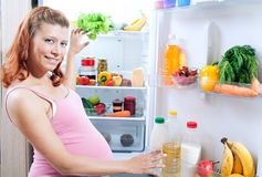 Pregnant woman and refrigerator with health food Royalty Free Stock Photo