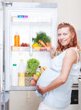 Pregnant woman and refrigerator with health food vegetables Royalty Free Stock Photography