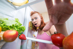 Pregnant woman and refrigerator with health food vegetables Stock Images