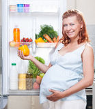 Pregnant woman and refrigerator with health food vegetables Royalty Free Stock Photos