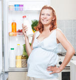Pregnant woman and refrigerator with health food vegetables Stock Photos
