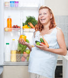 Pregnant woman and refrigerator with health food vegetables Royalty Free Stock Photo