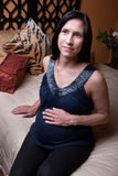 Pregnant Woman Relaxes. Beautiful pregnant Hispanic lady relaxes on bed Royalty Free Stock Photo