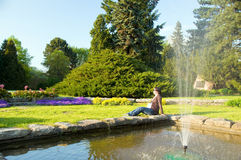 Pregnant woman relaxing. At fountain in the garden Stock Photo