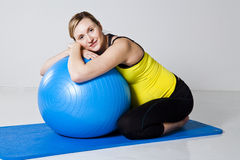 Pregnant woman relaxing against fitness ball Stock Photos