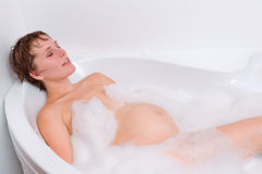 Pregnant woman is relaxing in the bath Royalty Free Stock Images
