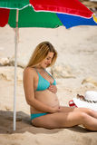 Pregnant woman relaxing on beach and holding hands on stomach Royalty Free Stock Images